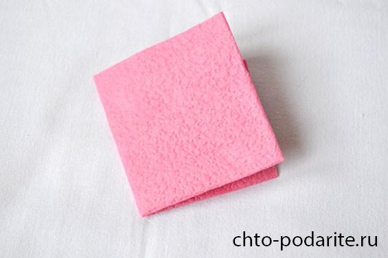 Сложенная вчетверо розовая салфетка