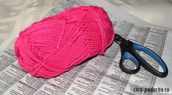 Газета, ножницы и нитка для вязания