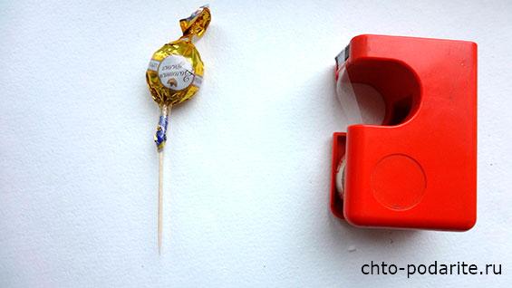 Берем конфету и при помощи скотча фиксируем ее на зубочистку