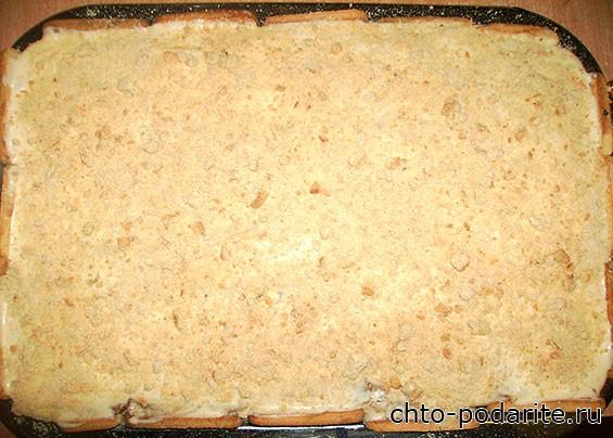 Края тортика обкладываем половинками печенья, посыпаем его крошками