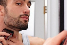 Мужчина бреет бороду электробритвой