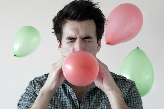 мужчина надувает воздушный шар